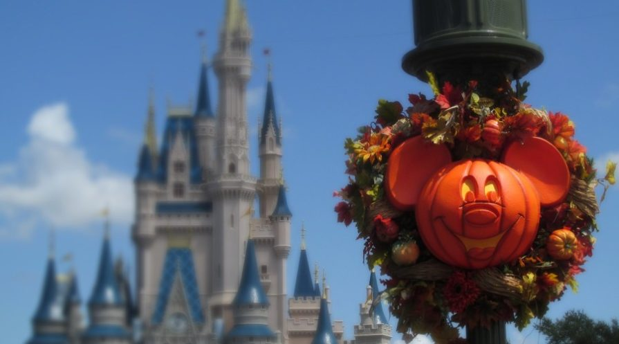 Pumpkin carved like Mickey Mouse in a wreath on a post at Disneyland