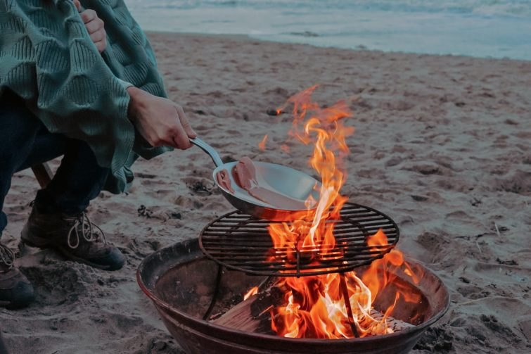 A person cooking bacon on a fire pit grill on the beach