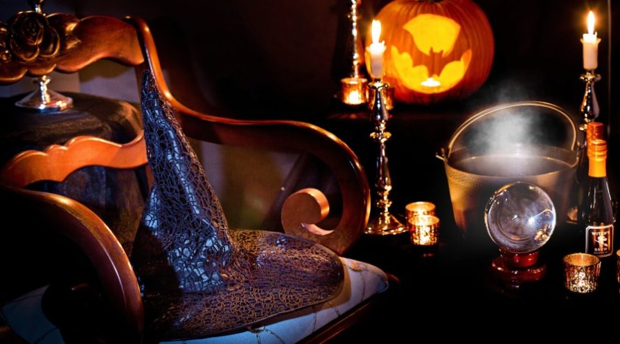 Witch hat on a chair with Halloween paraphernalia in background