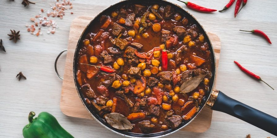 Beef stew in a pan on a cutting board