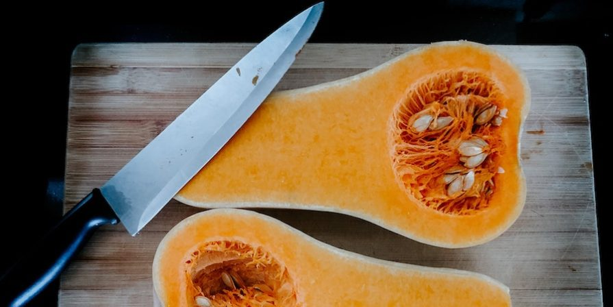 Halved butternut on cutting board with sharp knife