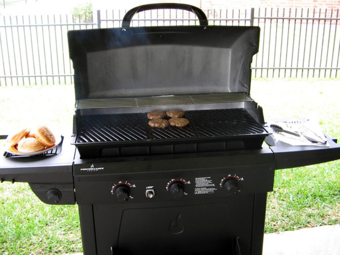 Gas grill with burgers on a grill grate