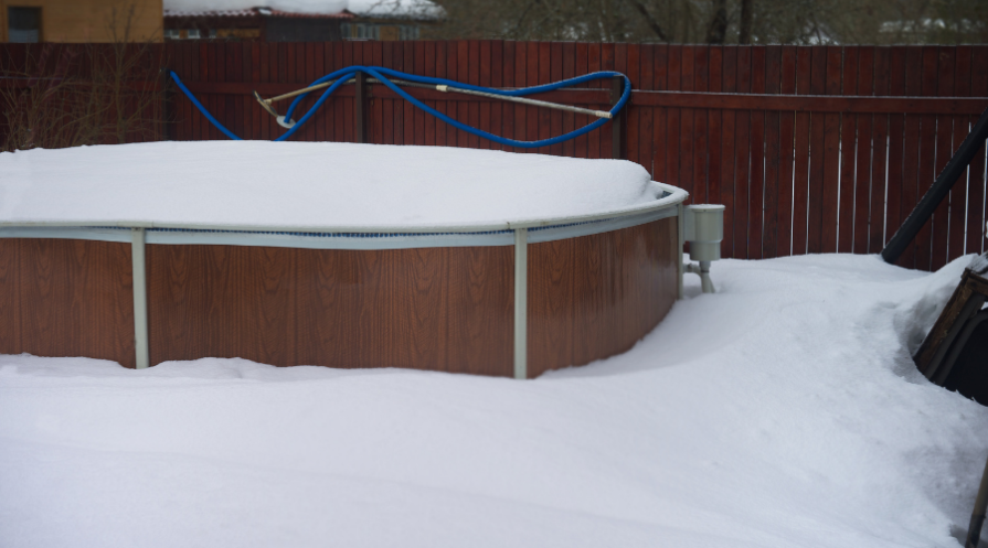 Above-ground pool covered with snow