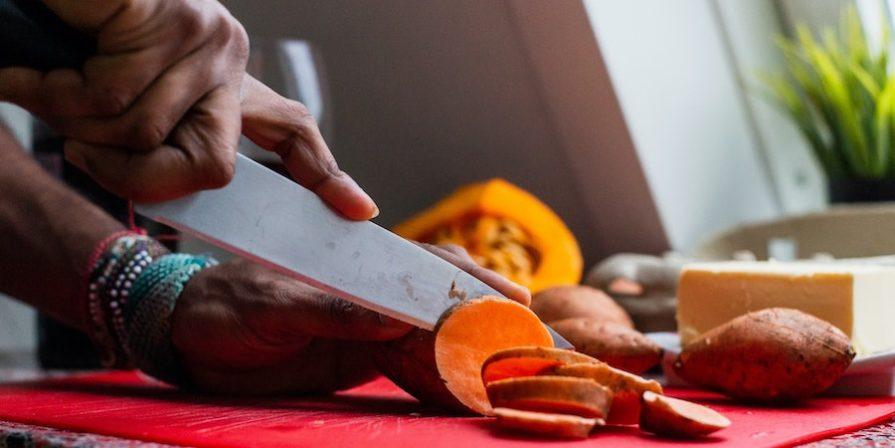 Hands cutting up a sweet potato