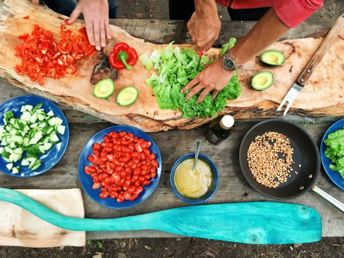 People cutting veggies on a wooden table
