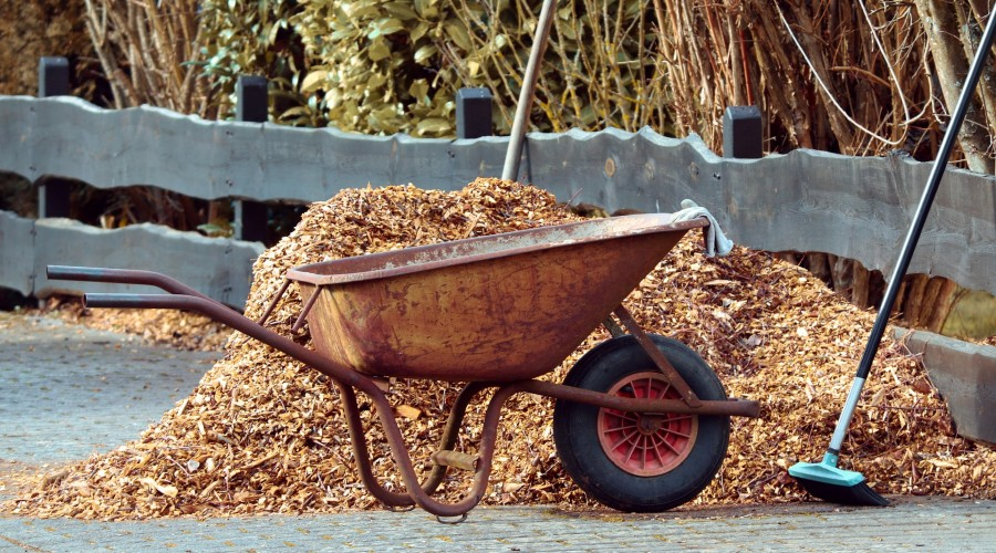 broom and wheelbarrow next to a pile of wood chip mulch